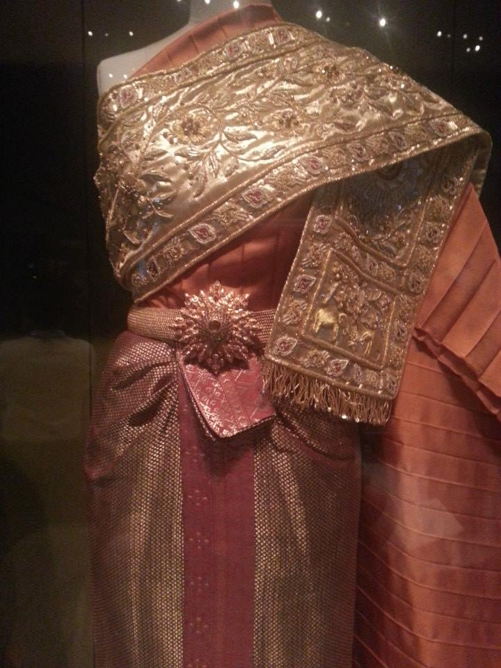 "Details of one of HMQ""s traditional Thai dress styles – metallic gold embroidered sash and gold and silk cloth."