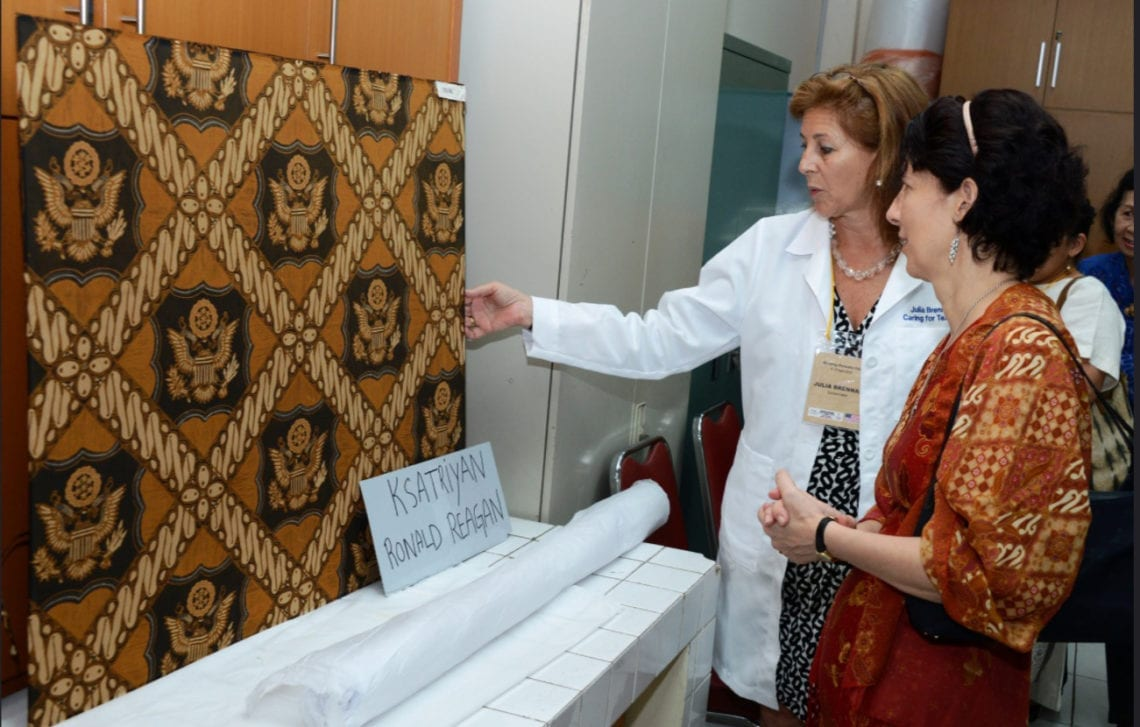 "Julia and and Chargé Kristen Bauer looking at the ""Reagan Ksatriyan"" batik, The name refers to the traditional Javanese court design of the diagonal pattern with motif in center, usually a garuda, but for Reagan's state visit in 1986, Iwan Tirta designed this hand batik with the Great Seal, and crafted it into the formal dress shirt."