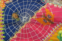 Spiderwebs are a fairly common motif in crazy quilts, but it is much rarer to find a fuzzy spider at home in it.
